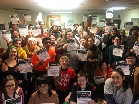 """Image of a pre-COVID collective meeting. The fliers read: """"Help trans women get out of ICE detention"""""""