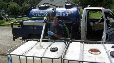 Seth True of Best Septic Service pumps urine from a 275-gallon tank for transfer to the farm. A family of three can produce this much urine in eight months. - PHOTOGRAPH BY ABE NOE-HAYS, RICH EARTH INSTITUTE
